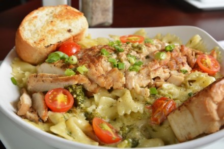 Closeup of chicken on bowtie pasta with a creamy pesto sauce, shallow depth of field